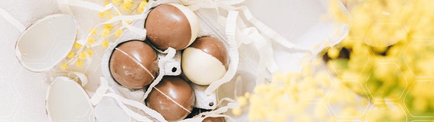 Ovos de Páscoa em embalagem rústica e flores ao lado