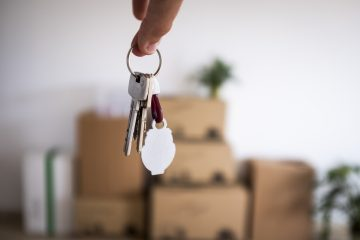 chaves de casa com caixas de mudança ao fundo
