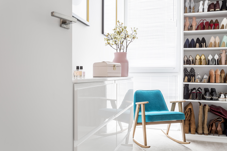 closet elegante com sapateira alta, poltrona verde e arranjo de flores