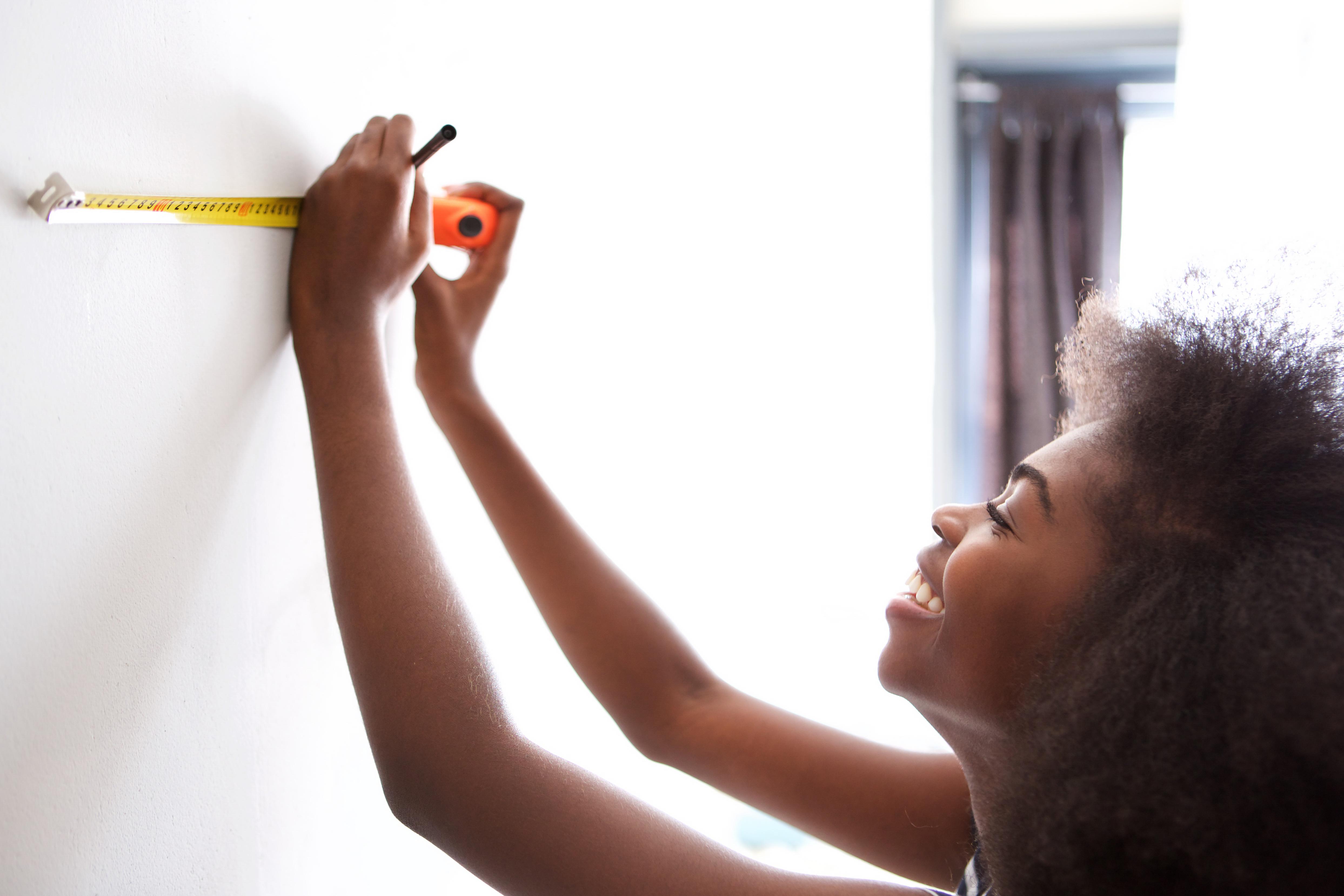 mulher medindo parede com trena