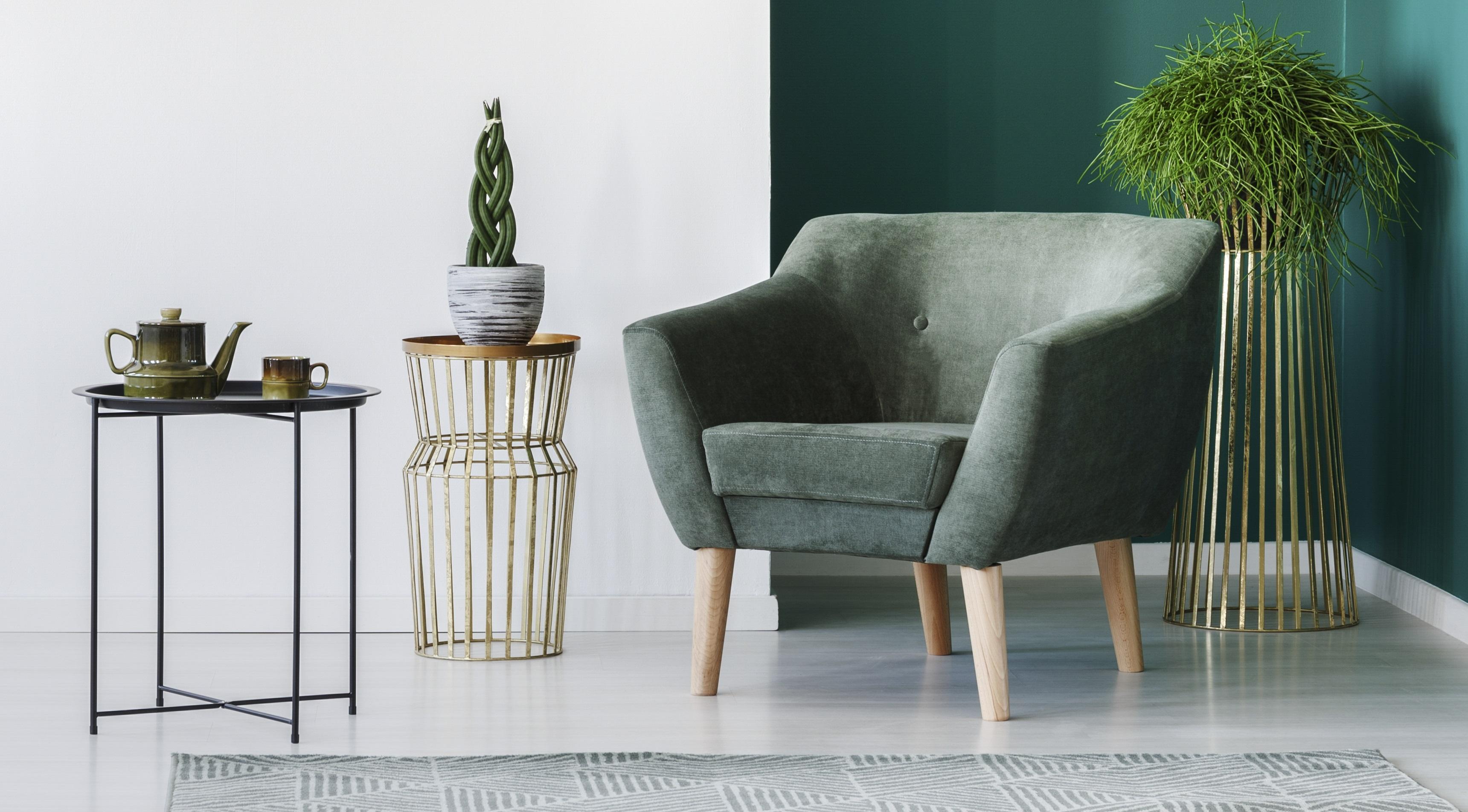 sala minimalista com parede e poltrona verdes, mesas de apoio e folhagem