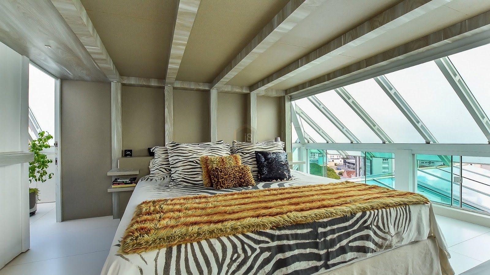 quarto em ático com colcha estampada e decoração extravagante