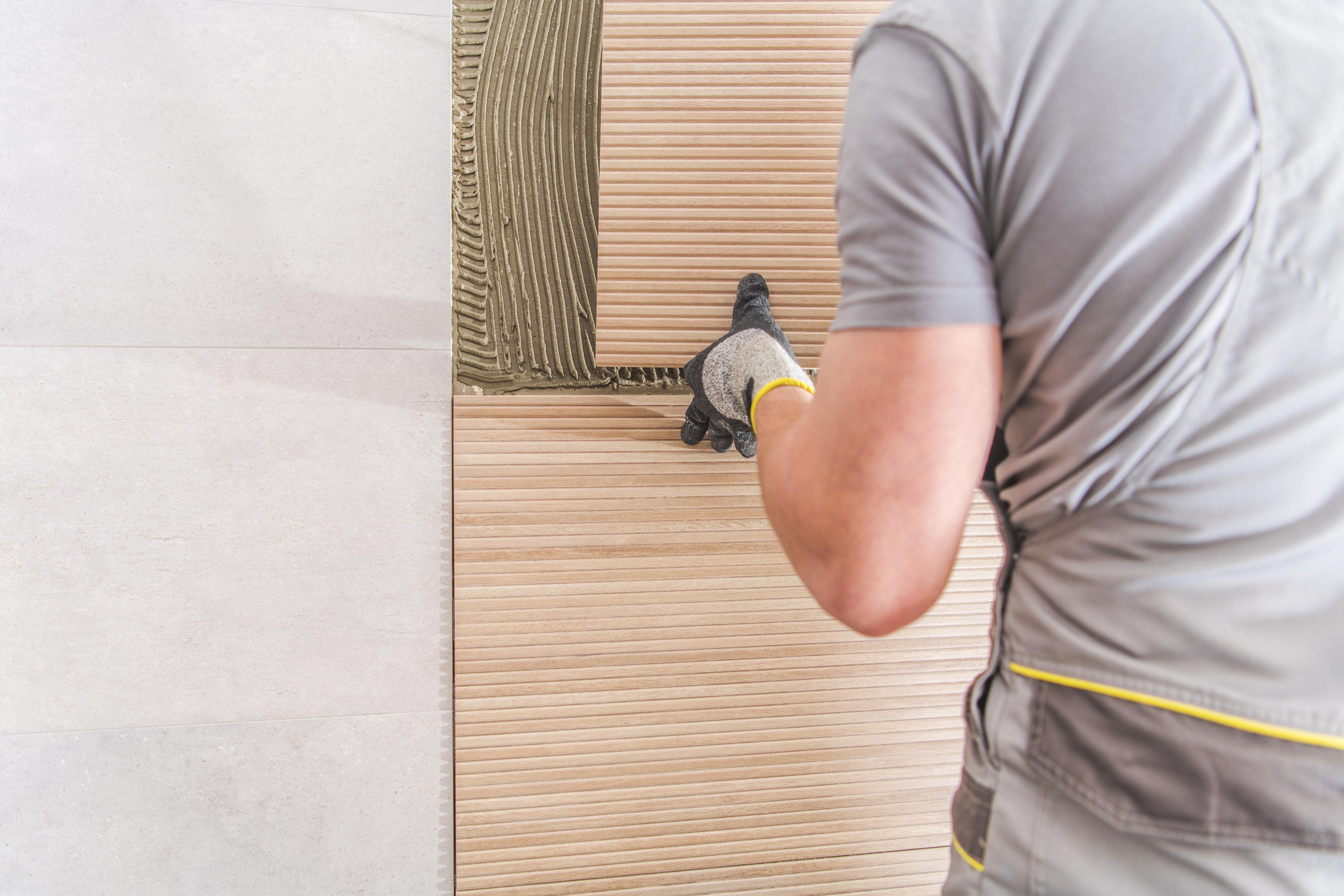 homem colocando revestimentos sustentáveis em parede