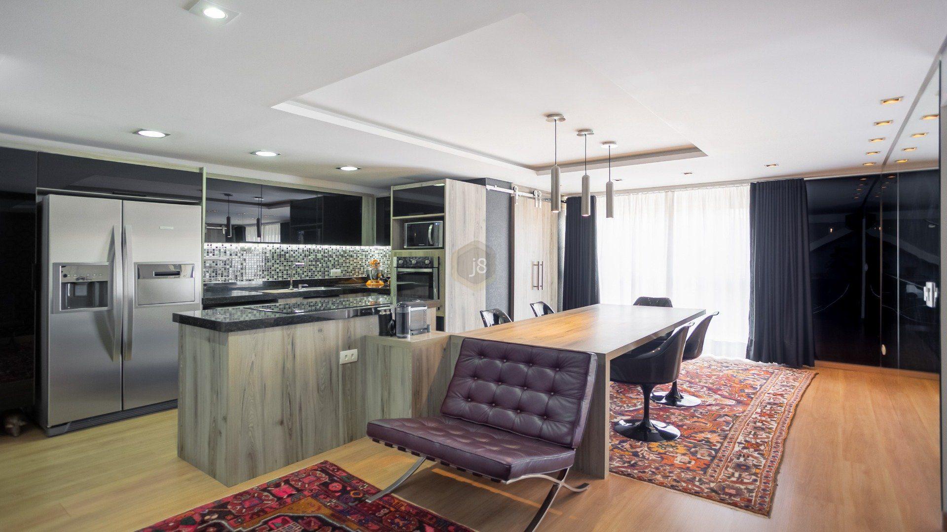 cozinha moderna integrada a sala de estar com poltrona roxa